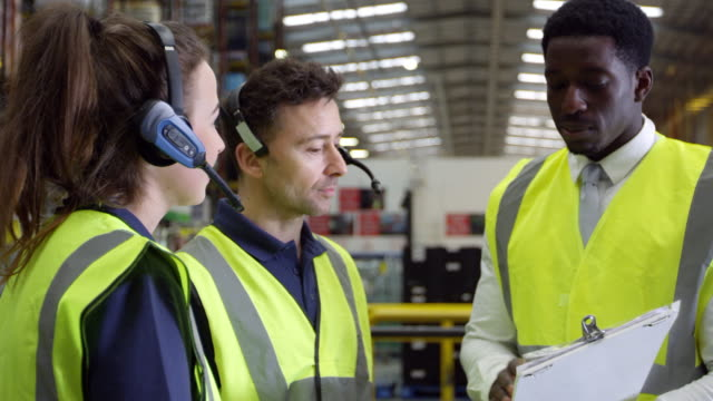 Discussion between staff members in a warehouse, shot on R3D Discussion between staff members in a warehouse, shot on R3D occupational safety and health stock videos & royalty-free footage