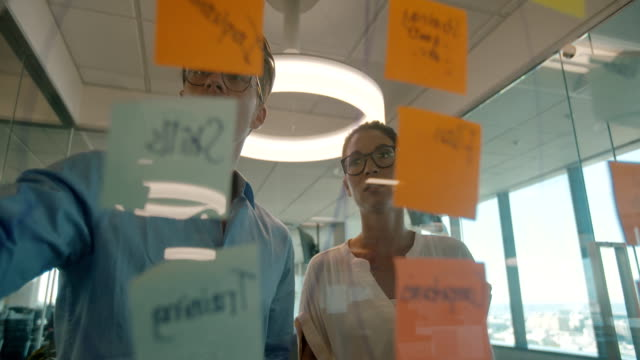 discussion over sticky notes on glass wall - biznes finanse i przemysł filmów i materiałów b-roll