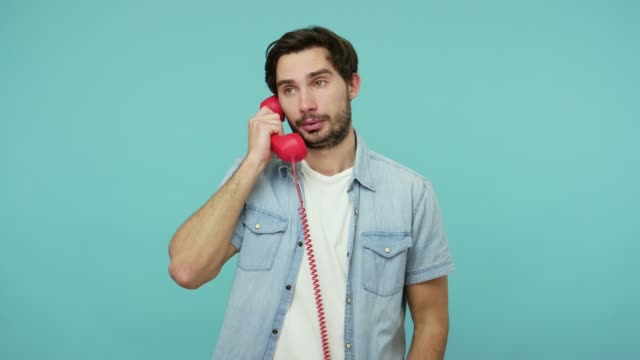 Disgruntled guy in jeans shirt answering phone call, customer communicating with contact center, talking on red telephone handset Disgruntled guy in jeans shirt answering phone call, customer communicating with contact center, talking on red telephone handset with displeased annoyed expression. indoor studio shot blue background prop stock videos & royalty-free footage