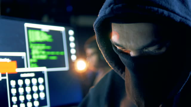 Disguised face of a male hacker while working in a close up Disguised face of a male hacker while working in a close up. 4K identity theft stock videos & royalty-free footage