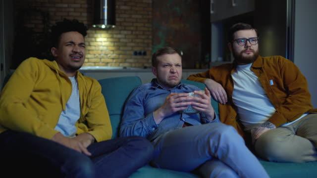 ekel emotionen auf gesichter von drei männlichen freunden sehen film zusammen zu hause - ekel stock-videos und b-roll-filmmaterial