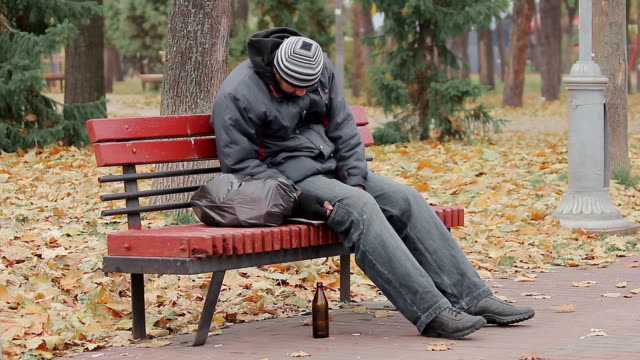 Disgusting drunk man sleeping and coughing on bench in city park, alcohol addict