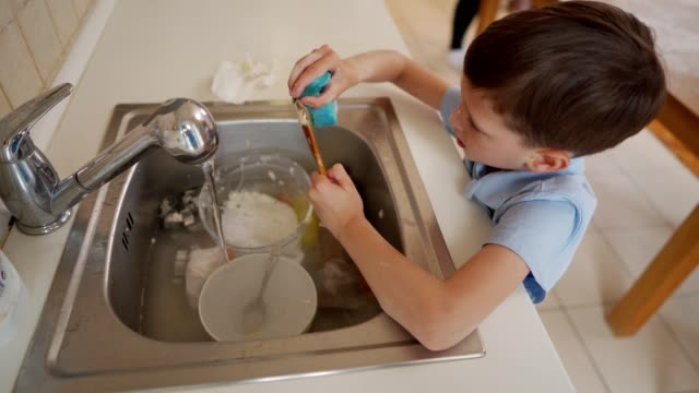 Dishes will be super clean when I'm done Little boy is washing dishes in the kitchen. kitchen sink stock videos & royalty-free footage