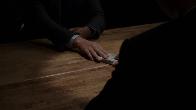 暗い部屋で会議でパートナーにお金を与える不正直なビジネスマン - 合意点の映像素材/bロール