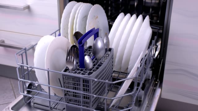Dishwasher baskets with dirty white dishes and cutlery in the kitchen. video