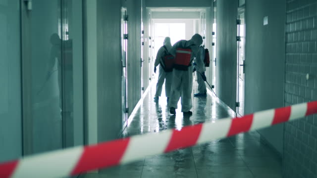 Disinfection, sanitation concept. Hallway is getting disinfected by workers in hazmat suits