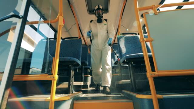 il disinfettante sta camminando lungo l'autobus e sanificarlo. prevenzione del coronavirus, processo di disinfezione sanitaria. - autobus video stock e b–roll