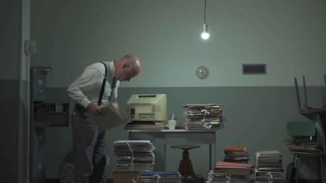 Disorganized businessman searching files in his office
