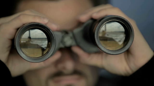 Dispatcher controls the air-traffic with binoculars in airport in control tower video
