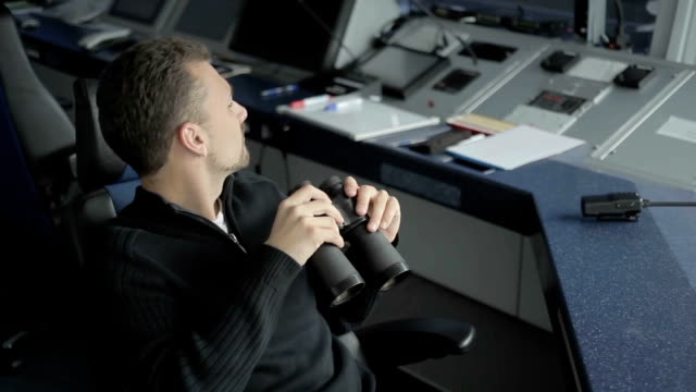 Dispatcher controls the air-traffic with binoculars in control tower in airport video
