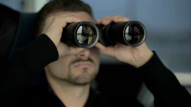 Dispatcher in airport controls the air-traffic with binoculars video