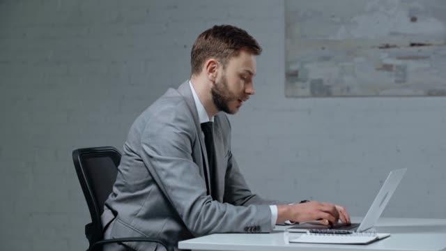 オフィスでオンライン賭けをする不愉快なビジネスマン - 不吉点の映像素材/bロール