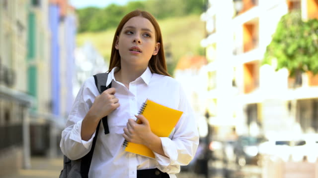Displeased female student with backpack and books looking into camera, education