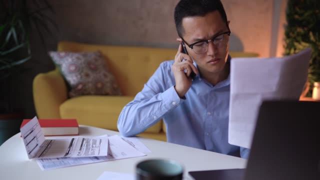 vídeos de stock, filmes e b-roll de homem japonês desagradado que fala ao serviço de atenção a o cliente ao pagar contas em linha - dia do cliente