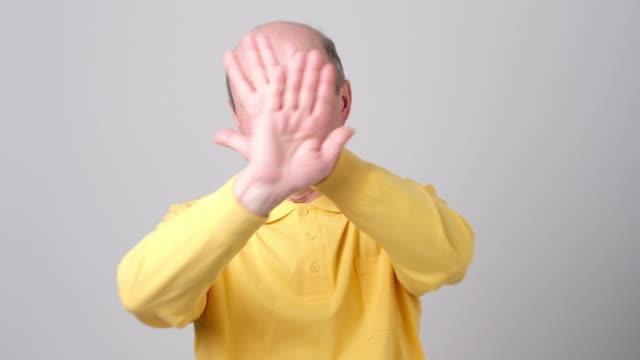 displeased mature man refusing, stretching hands to camera - negacja filmów i materiałów b-roll