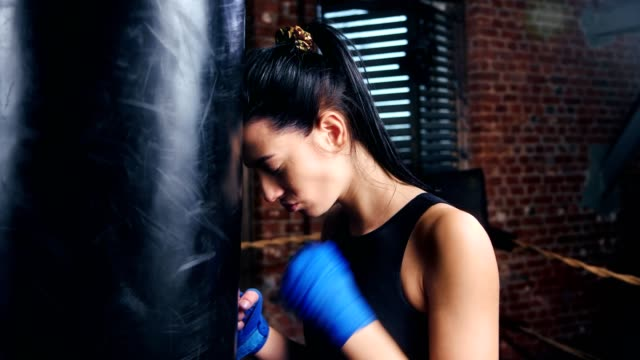 Displeased mma brunette girl wearing blue protective wrapped tapes on hands tired at training