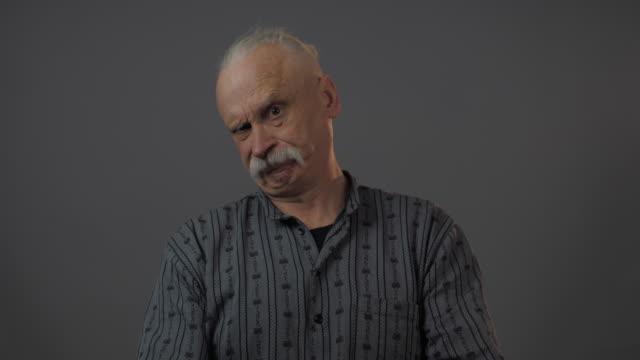 vídeos de stock e filmes b-roll de displeased old man shakes head negatively raising eyebrow - sobrancelha