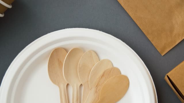 disposable dishes of paper and wood recycling and eco friendly concept - disposable dishes of paper and wood on grey background kitchen utensil stock videos & royalty-free footage