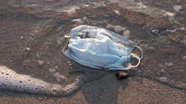 maschere facciali usa e getta e detriti di plastica sulla spiaggia nella zona del surf. coronavirus covid-19 sta contribuendo all'inquinamento, poiché le maschere usate scartate ingombro inquinano le spiagge urbane insieme alla spazzatura di plastica - inquinamento video stock e b–roll
