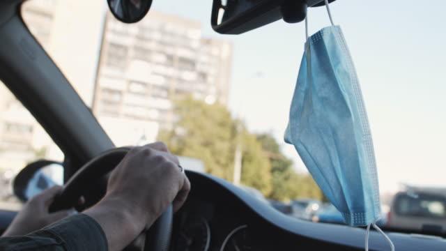 stockvideo's en b-roll-footage met een wegwerp beschermend masker dat op achteruitkijkspiegel van de auto hangt - mirror mask