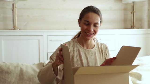 Dissatisfied female customer open cardboard box receive damaged parcel