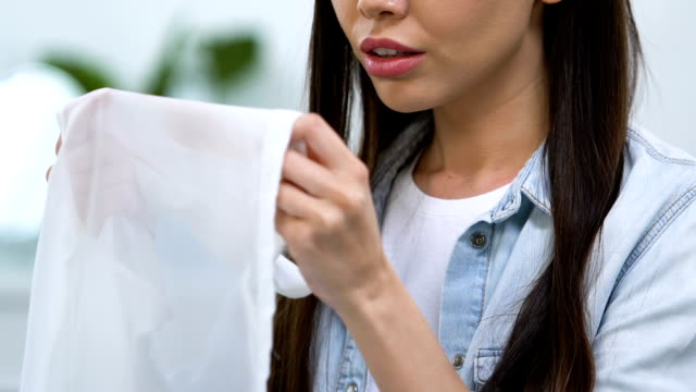 Dissatisfied girl showing blouse with coffee stain on blouse, laundry problems
