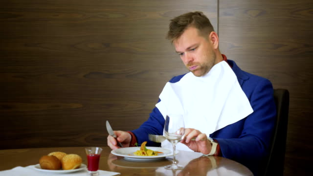 Dissatisfied restaurant critic looking on dish and does not want to try it Dissatisfied restaurant critic looking on dish and does not want to try it. Young man sitting without appetite before dish on table in cafe during business lunch negative emotion stock videos & royalty-free footage