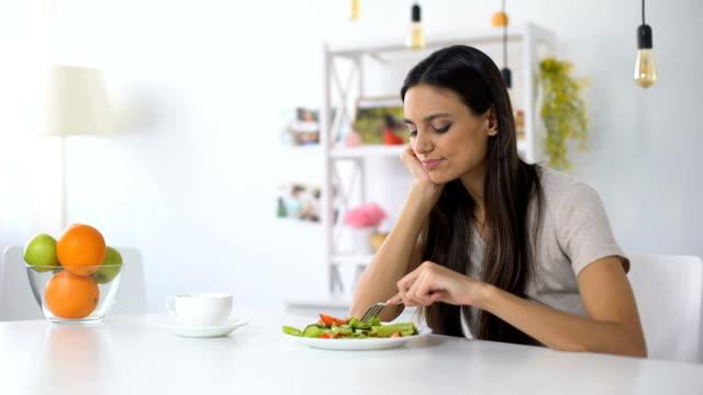 サラダを見て不満の女性、減量のための健康的な低カロリーの食事 - 体への関心点の映像素材/bロール