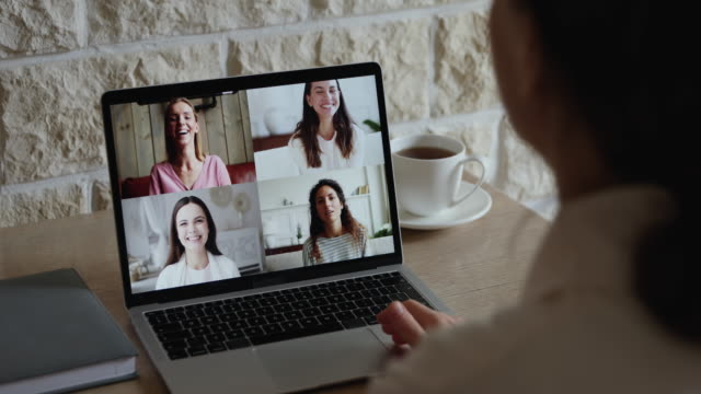 Distance friends chatting by video call using computer videoconference app
