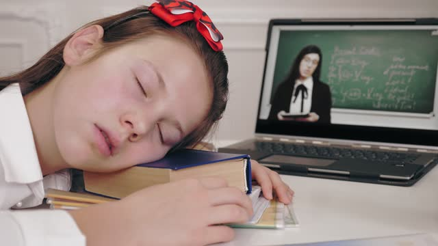 distance learning, online schooling. tired, exhausted schoolgirl fell asleep on desk in front of laptop screen while watching tutorial video lesson. Distant education, online schooling, e-learning video