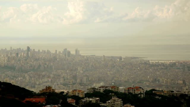 Distant city timelapse Time lapse of city of Beirut, Lebanon from the distance. Nearest plane shows few suburban homes on the hillside, while the bustling city stretches in the distance. Fat cumulus clouds roll across the sky, allowing the Sun to shine trough. beirut stock videos & royalty-free footage