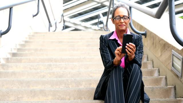 distinguished senior african american businesswoman texting - breast cancer awareness filmów i materiałów b-roll