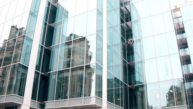 パリのオフィスセンターの近代的なガラスのファサードで古い建物の歪んだ反射。古いものと新しい、反対の概念。フルhdステディカムビデオ - スタビライザー使用点の映像素材/bロール
