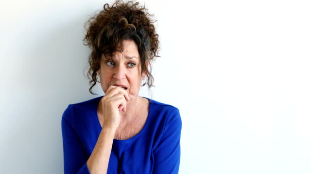 Distraught anxious Mature Caucasian female sitting against white wall 4k video