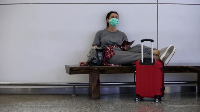 vídeos de stock e filmes b-roll de distraught, stressed, tired girl traveler with a medical mask on her face is waiting for missed, delayed or canceled flight due to a coronavirus. passenger spending a night at airport due to covid-19 - covid flight