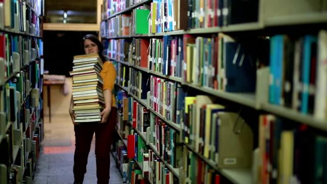 nödställda flicka söker efter böcker - bära bildbanksvideor och videomaterial från bakom kulisserna