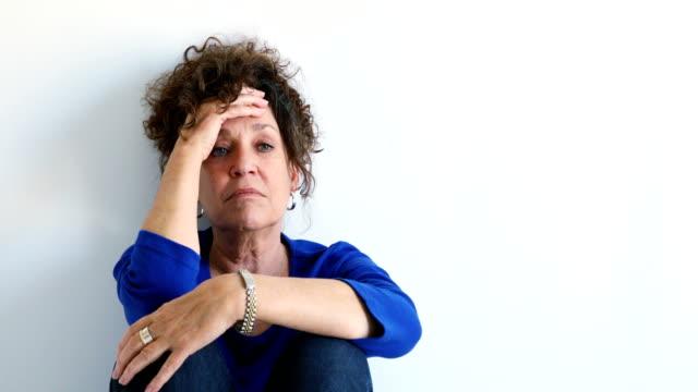 distressed mature caucasian female sitting against white wall 4k - wine filmów i materiałów b-roll