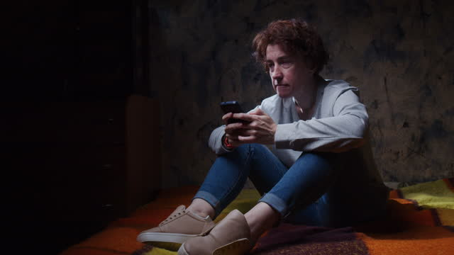 Distressed woman is sitting on the sofa in dark room and holding phone in contemplation video