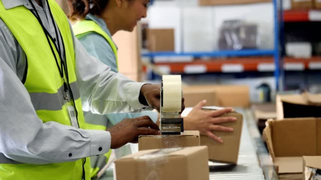 Distribution warehouse employees prepare packages to be sent to customers video