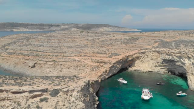 dive resort, drone view of sea lagoons with pleasure boats and yachts and vacationers people tourists swim in turquoise water between islands dive resort, drone view of sea lagoons with pleasure boats and yachts and vacationers people tourists swim in turquoise water between rocky islands malta stock videos & royalty-free footage