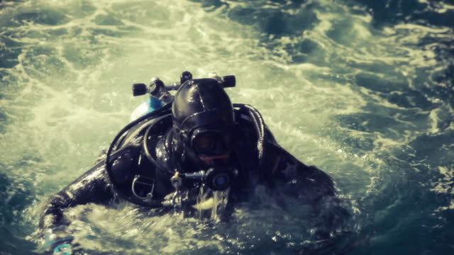 Diver preparing to go into water Man in a diving suit half submerged in water scuba diving stock videos & royalty-free footage