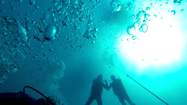 Divers swimming underwater intending to rise to surface, air bubbles in water Divers swimming underwater intending to rise to surface, air bubbles in water aqualung diving equipment stock videos & royalty-free footage