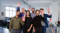istock Diverse business group waving together and smiling 1201225355