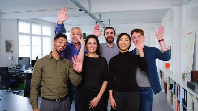 vielfältige unternehmensgruppe winkt zusammen und lächelt - person gemischter abstammung stock-videos und b-roll-filmmaterial