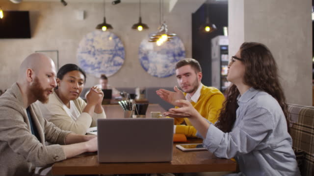 Diverse Business Team Discussing Project on Laptop in Cafe