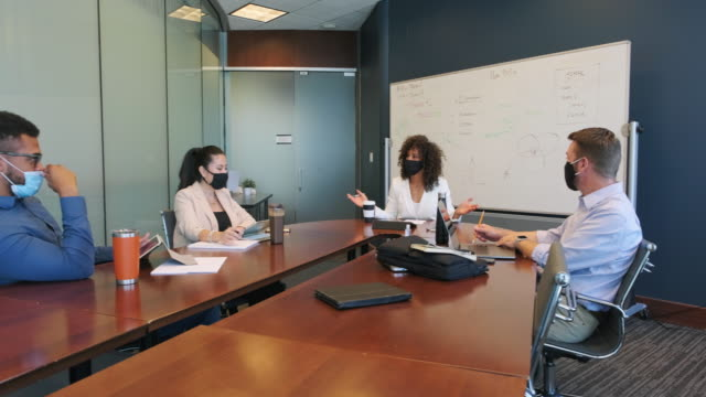 diverses business-team in einem meeting mit schutzmasken - finanzwirtschaft und industrie stock-videos und b-roll-filmmaterial