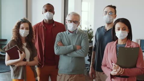 ofiste kameraya poz veren yüz maskelerinde farklı i̇ş ekibi - office stok videoları ve detay görüntü çekimi