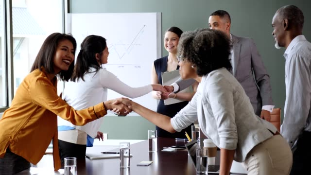 Diverse businesspeople greet one another before meeting