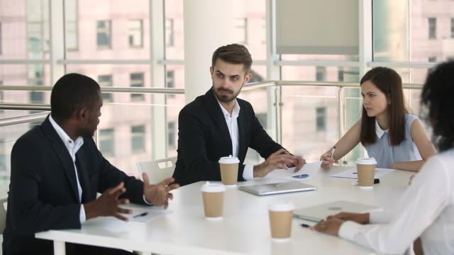 Diverse businesspeople in formal wear negotiating during meeting in boardroom