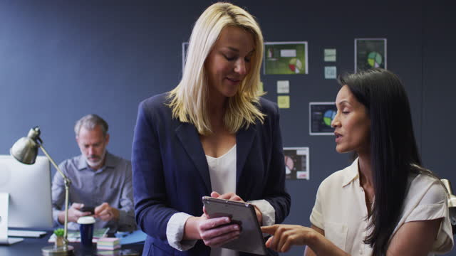 Diverse businesswomen using digital tablet discussing in office male colleague behind